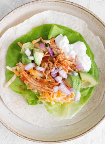 cilantro lime salsa chicken shredded in a flour tortilla with lettuce, onion, sour cream, and cheese