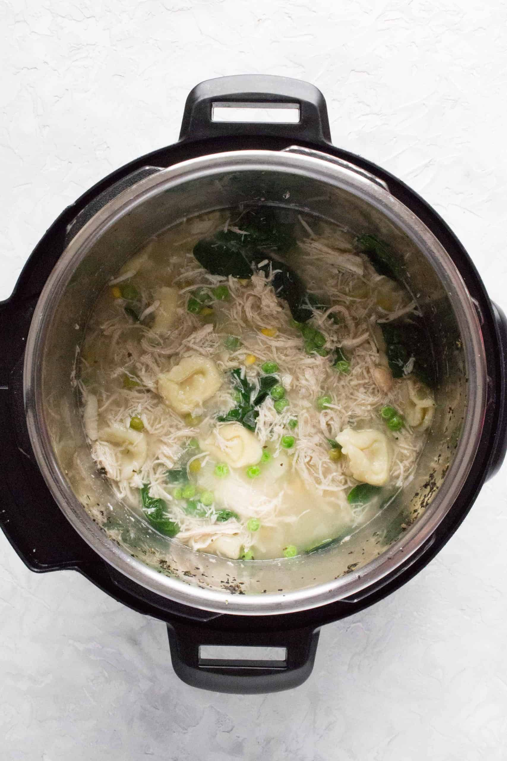 instant pot with cooked chicken and tortellini soup inside