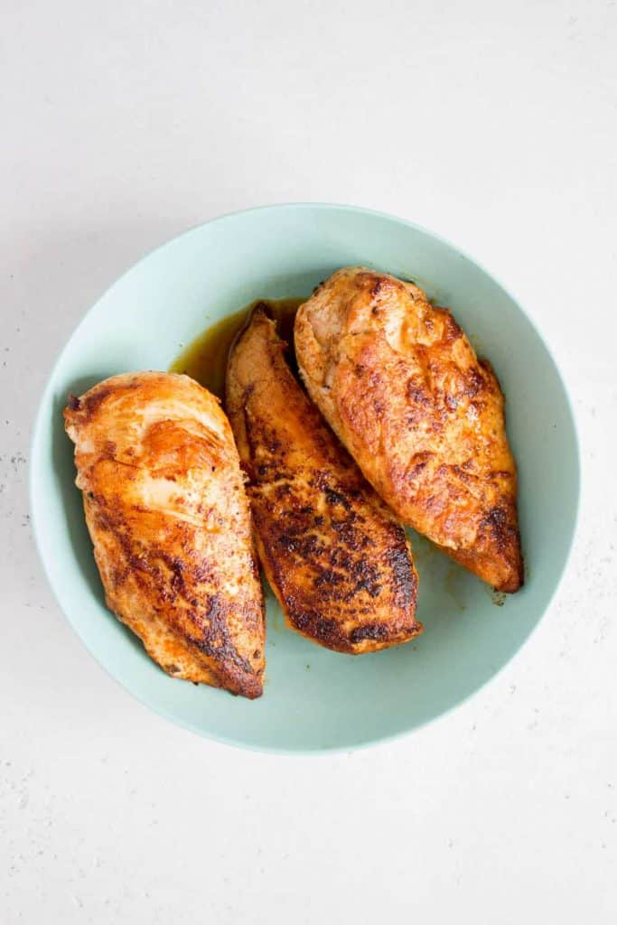 bowl with 3 pan seared chicken breasts