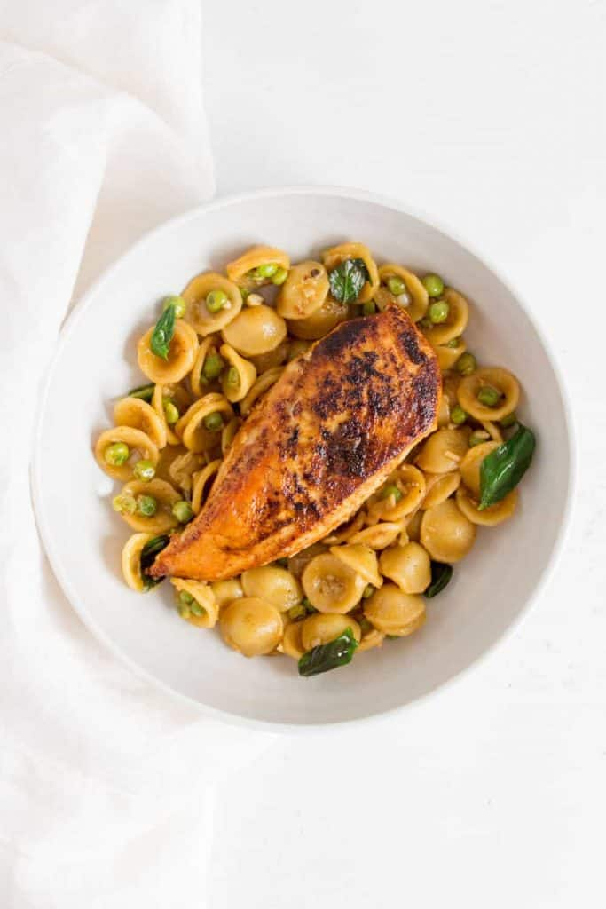 bowl with garlic lemon basil orecchiette with peas and pan fried chicken breast