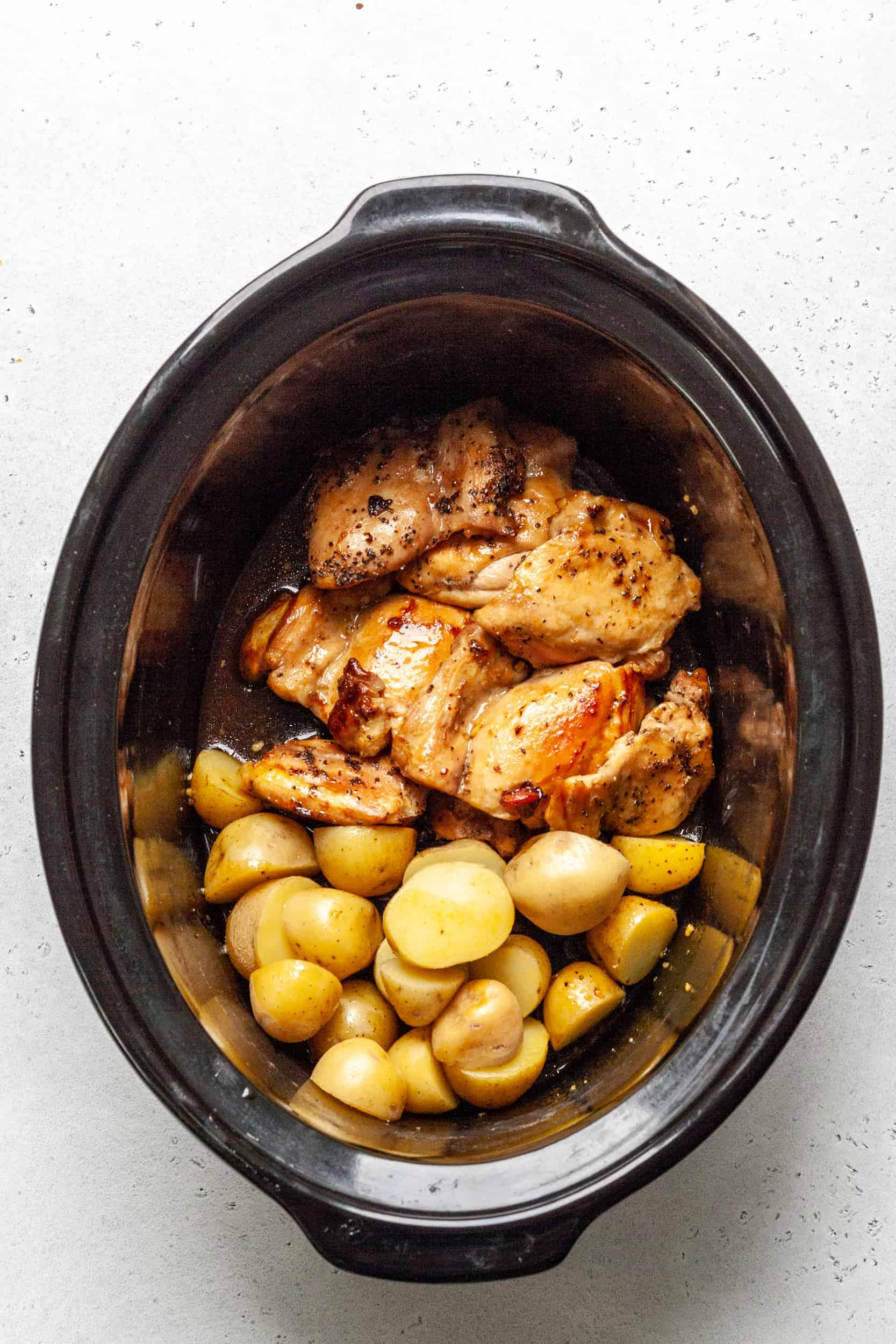Slow cooker with chicken thighs and potatoes with honey garlic.