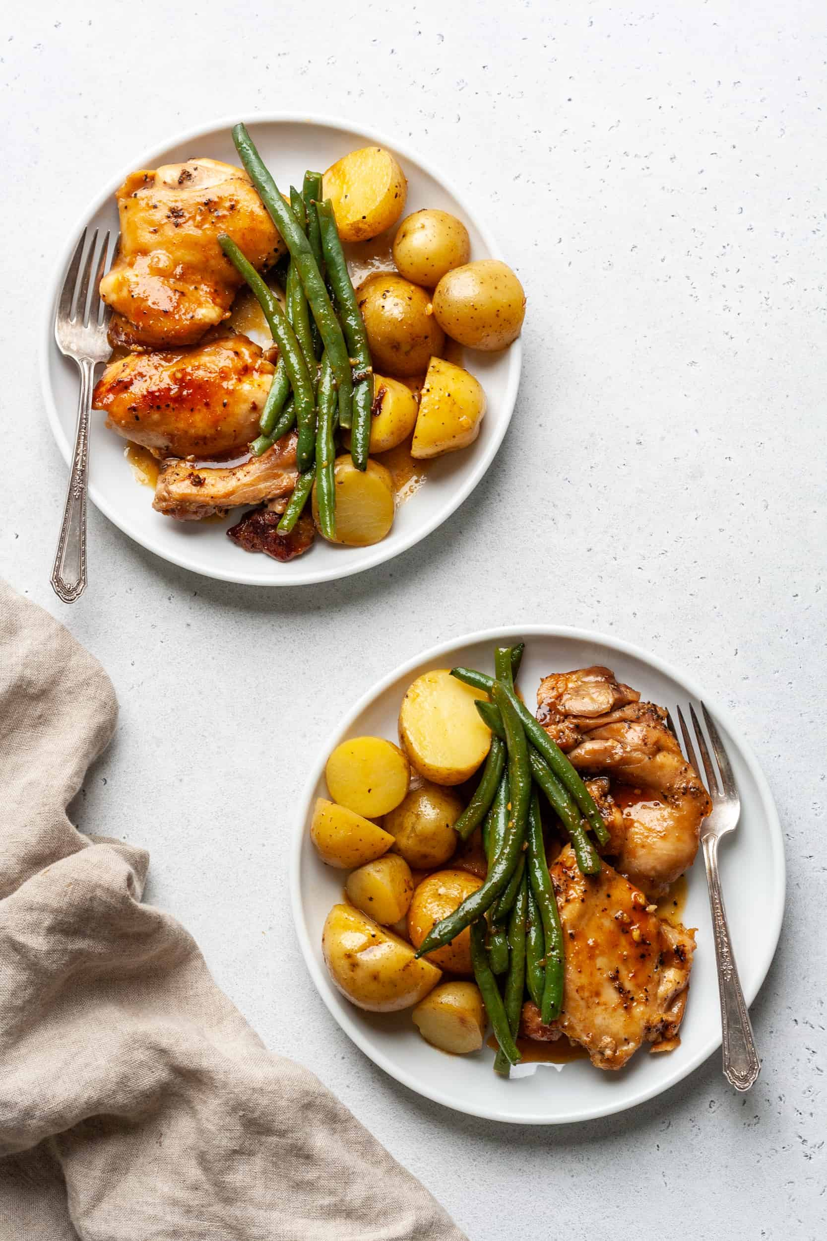 Two plates of chicken and potatoes with green beans.