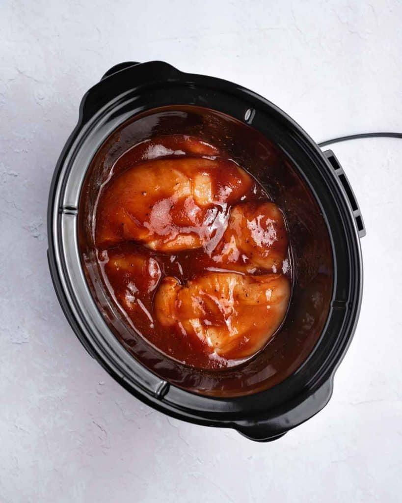 BBQ sauce added to the chicken in the slow cooker.
