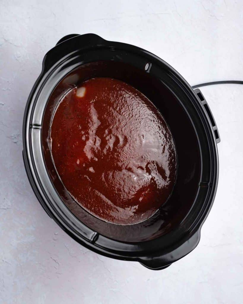 BBQ sauce added to a slow cooker.