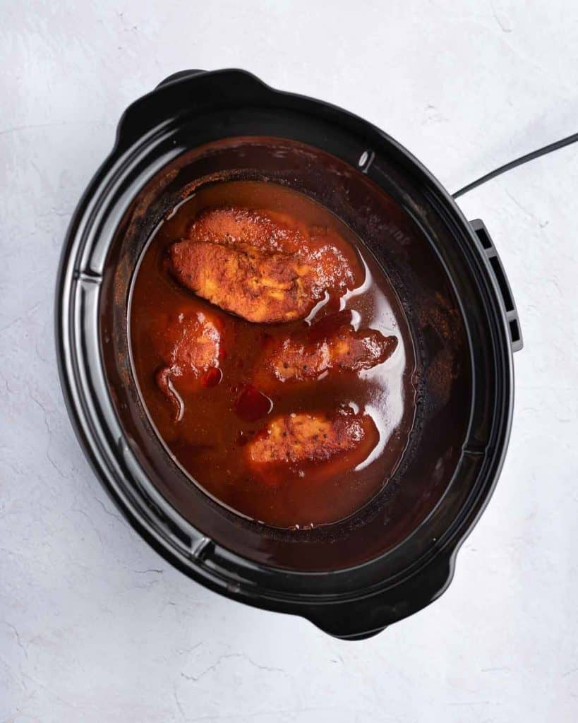 Cooked chicken in the slow cooker with bbq sauce.