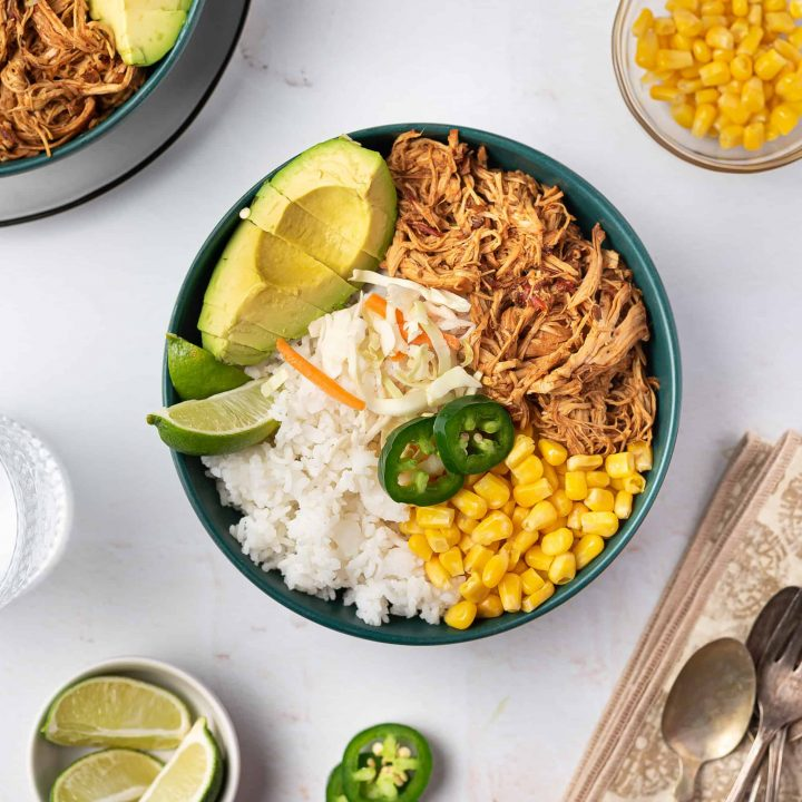 Overhead view of a bowl of shredded honey chipotle chicken with corn, avocado, and lime.