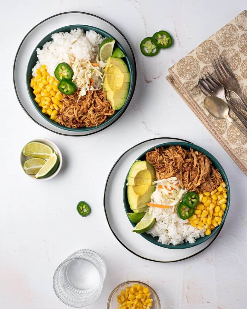 Overhead view of two bowls of slow cooker honey chipotle chicken rice bowls.