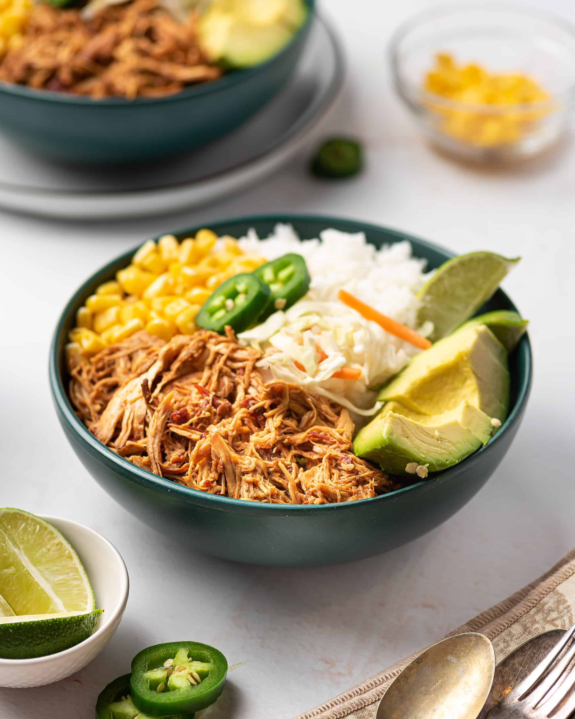 A rice bowl with avocado, honey chipotle chicken, corn, lime wedges, and jalapenos.