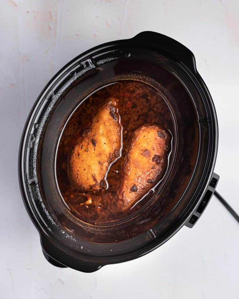 Cooked chicken breasts in a slow cooker.