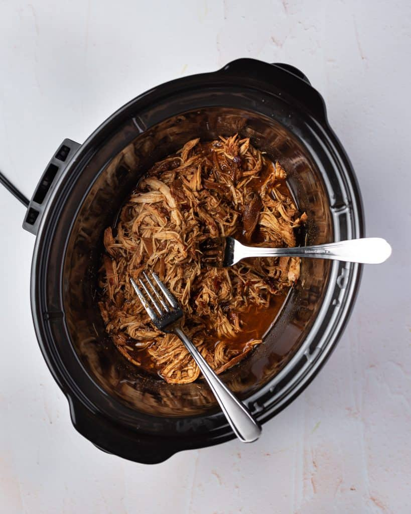 Overhead view of honey chipotle chicken shredded in a slow cooker.