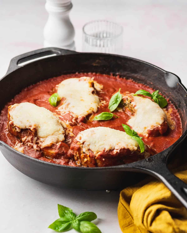 Mozzarella chicken in a cast iron with fresh basil.