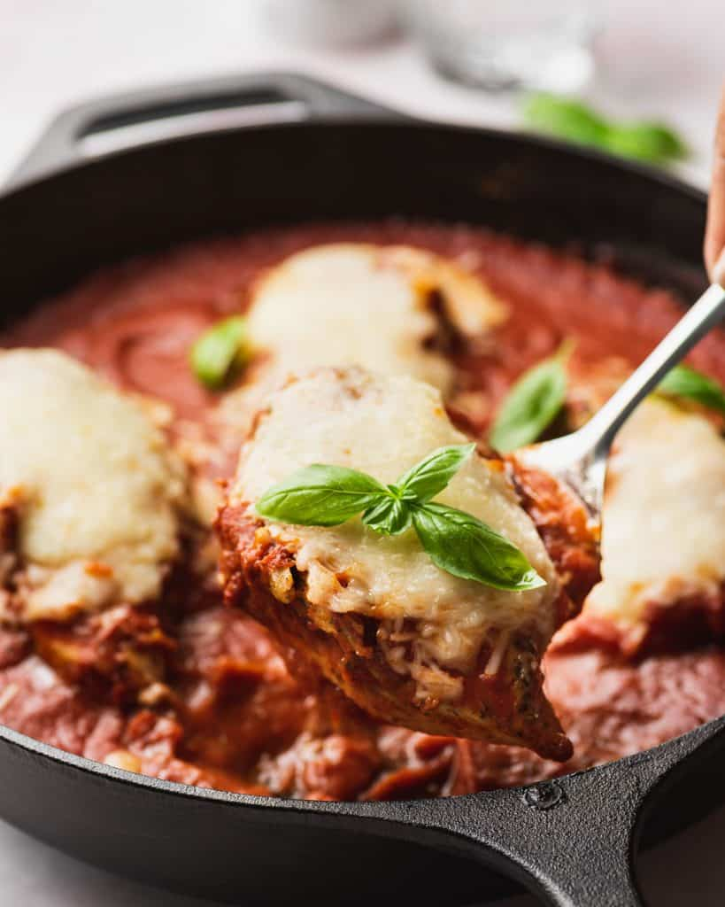 Mozzarella chicken being lifted from a pan.