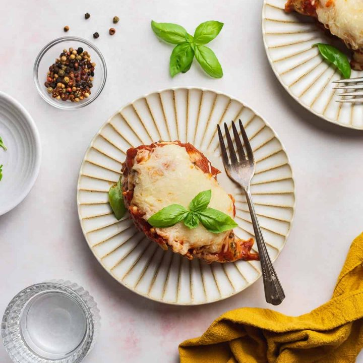 Overhead view of a scalloped plate with mozzarella chicken with a fork.