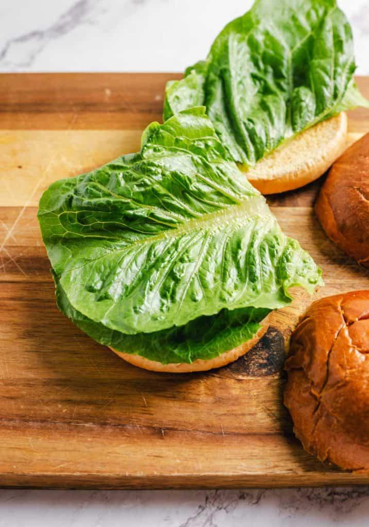 Lettuce added to a bun.