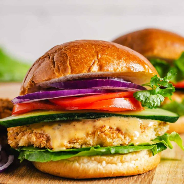 Chicken sandwich with toppings on a cutting board.