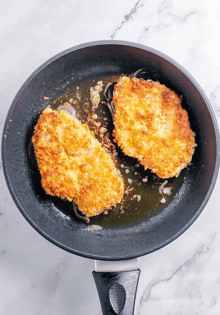 Fried chicken cutlets in a pan.