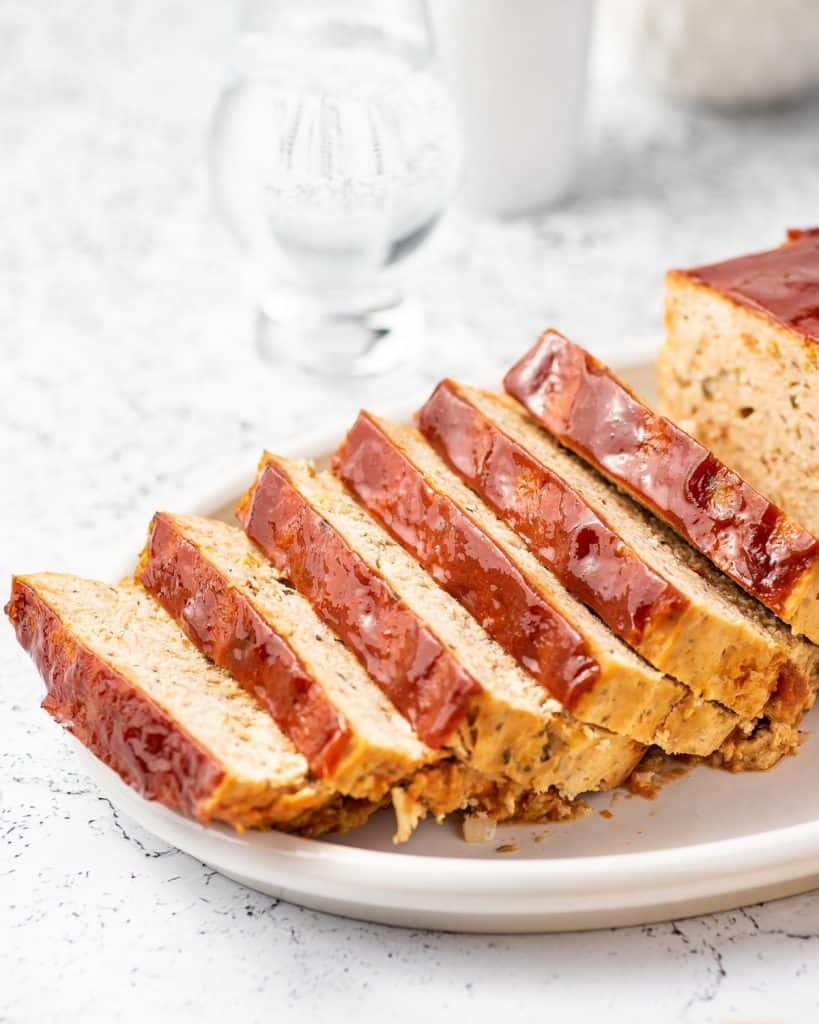 A chicken meatloaf being sliced on a plate.