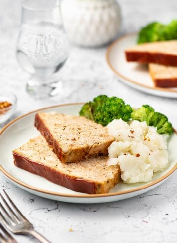 A plate with two slices of chicken meatloaf with mashed potatoes and broccoli.
